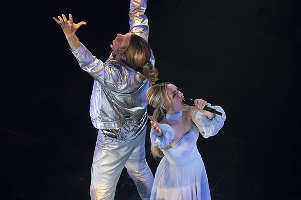 Will Ferrell and Rachel McAdams singing on stage in white matching outfits.