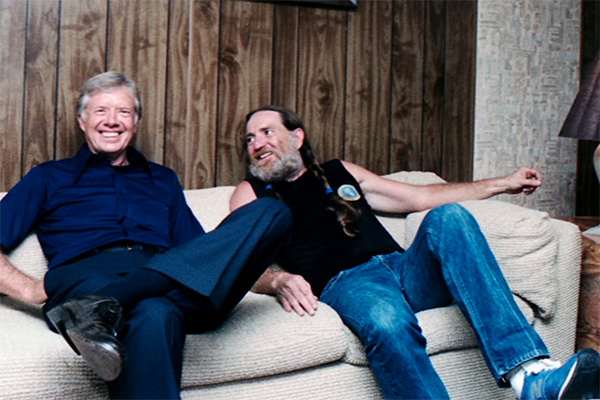 Willie Nelson and Jimmy Carter sit on a couch.