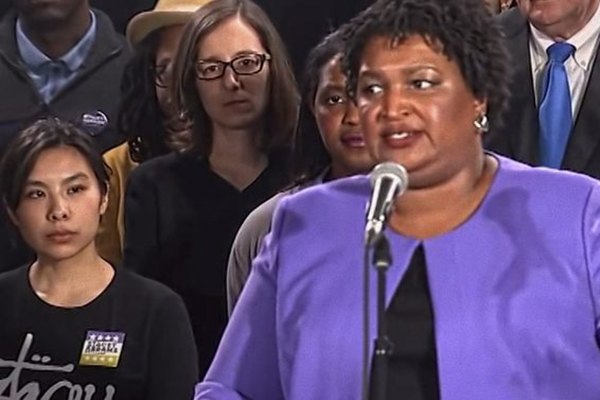 Stacey Abrams, an American politician, lawyer, voting rights activist, and author who served in the Georgia House of Representatives from 2007 to 2017, serving as minority leader from 2011 to 2017 speaks at a podium.
